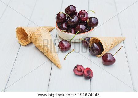 Bowl and cones filled with cherries on a wooden table