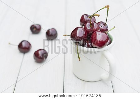 Mug filled with cherries on a wooden table