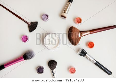 Makeup set. Brushes, powder, pigments on white background. Professional tools and eyeshadows for eye visage.