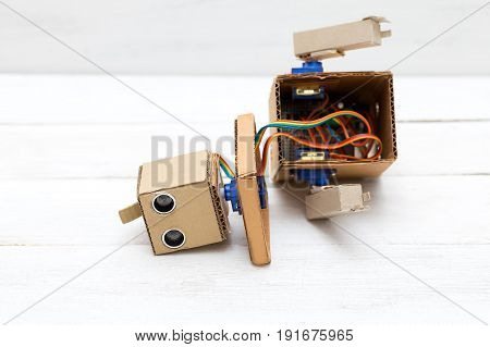 broken robot  with hand's on white wooden background
