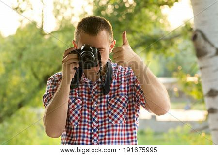 Photographer Takes Pictures Against The Background Of Greenery. Front View. Thumbs Up