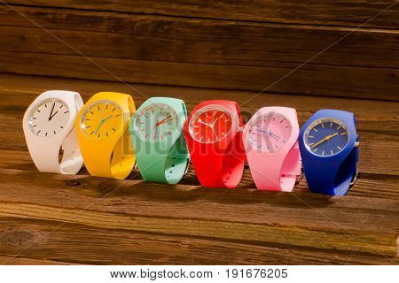 Multi-colored sports watch on a wooden background