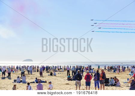 Weston-super-Mare United Kingdom - June 17 2017: A large crowd of people at the beach are watching the Red Arrows flying during the airshow in Weston-super-Mare.
