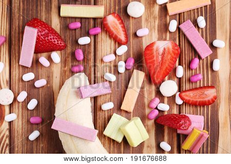 Chewing Gums With Strawberries And Bananas On Brown Wooden Table