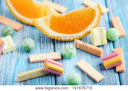 Different Chewing Gums With Orange On Blue Wooden Table