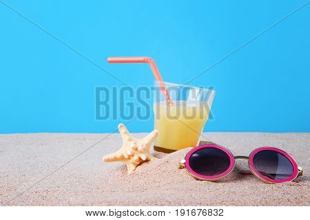 Pink Sunglasses With Glass Of Juice And Starfish On The Beach Sand