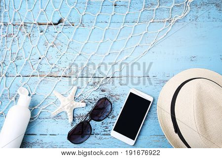 Sunglasses with smartphone hat and starfish on wooden table