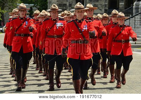 Victoria BC,Canada,June 10th 2014.RCMP police officers march in unison in Victoria BC wearing their red tunic uniforms..