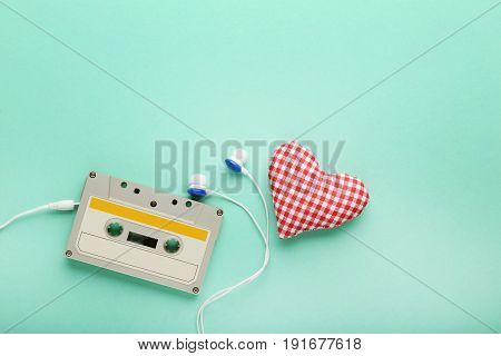 White Cassette Tape With Earphones On Mint Background