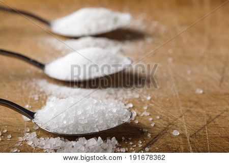 Close up of spoon filled with salt over wooden background