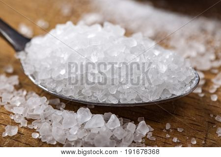 Close up of sea salt in stainless steel spoon over wooden background