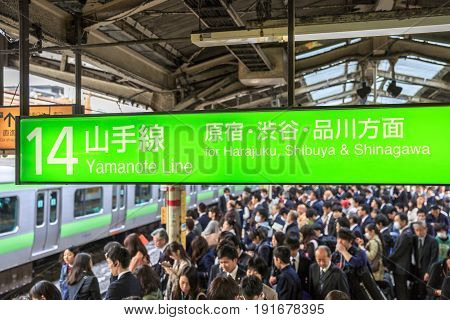 Tokyo, Japan - April 17, 2017: Yamanote Line signboard for Harajuku, Shibuya and Shinagawa, the most important train line in Tokyo. Crowd of people waiting for rail train at Tokyo main railway station
