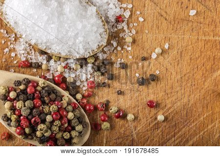 Wooden spoons with sea salt and peppercorns on wooden background with copy space