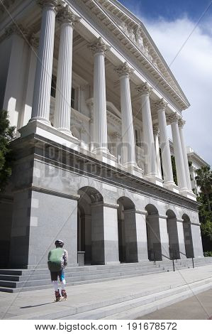 Man rollerskating down the front walkway of California's Capitol building in Sacramento.