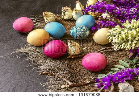 Wild flowers and dyed Easter eggs on rug of strawby the background of black plywood