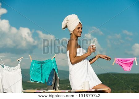 woman or happy housewife in terry towel hold coffee tea cup near iron and ironing board at underwear hang on clothesline rope on clothespin sunny outdoor on cloudy blue sky background