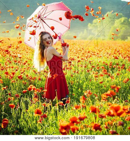 girl with long curly hair in red dress hold pink umbrella in field of poppy seed flower on green stem with petal in sky on natural background summer drug and love intoxication opium