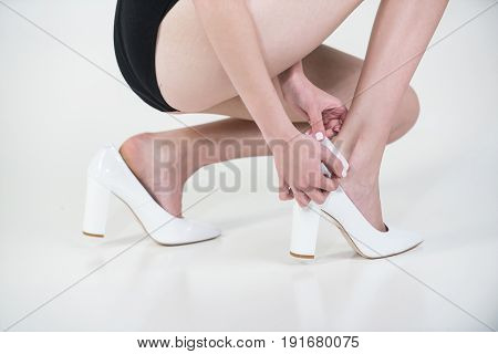 adhesive plaster on female leg with wound in fashionable shoes young girl isolated on white background skincare and health