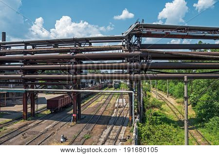 Rusty pipeline of the obsolete metallurgical enterprise under which passes the railway ways