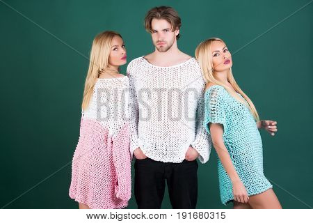 Young stylish people in fashionable sweaters stand on green background man and women twins