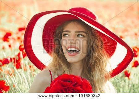 girl with long curly hair in red dress and retro hat hold flower bouquet in field of poppy seed on sunny natural background summer drug and love intoxication opium pin up woman