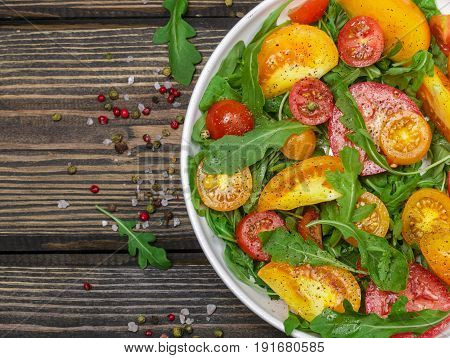 Fresh Salad Of Red, Pink And Yellow Tomatoes With Arugula And Spices In A White Plate On A Dark Wood