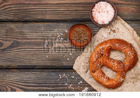 Pretzel With Caraway Seeds And Coarse Salt On A Dark Wooden Table. Selective Focus. Copy Space. Top