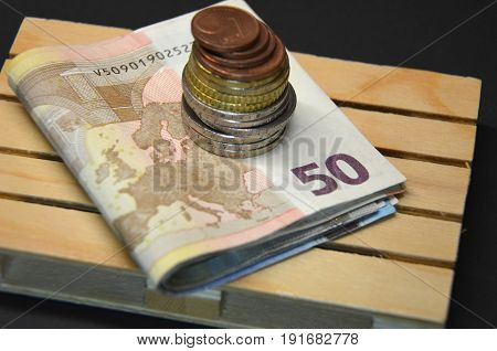 Stacked Euro banknotes and coin money on the pallet. Savings. Macro photo european currency.