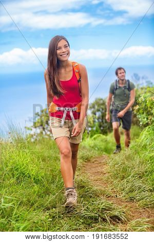 Happy woman hiker hiking couple in nature trek on hike trail on summer travel vacations. Healthy lifestyle young Asian girl smiling enjoying walk with man.