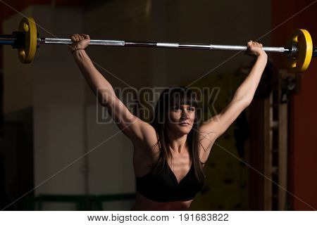 Woman Doing Press Exercise For Chest With Barbell