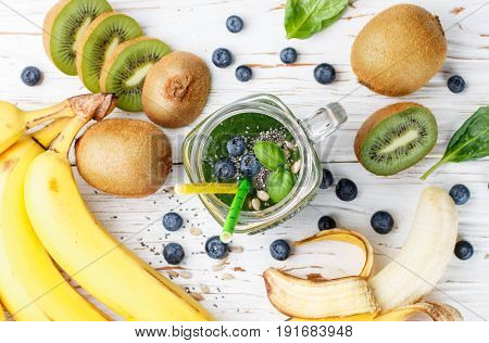 Healthy Green Smoothie And The Ingredients - Spinach, Banana, Kiwi, Chia Seeds, Sunflower Seeds And