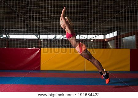 Fitness Woman Performing A Long Jump In Gym