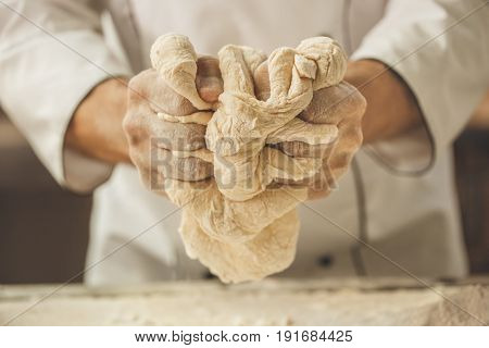 Bakery chef cooking bake in the kitchen professional knead dough