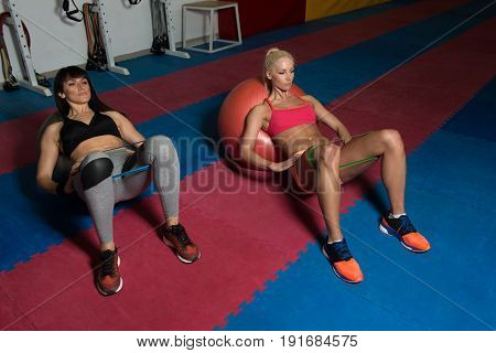 Couple Train Together With Resistance Bands On Ball