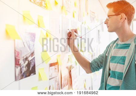 Creative businessman writing on paper in office