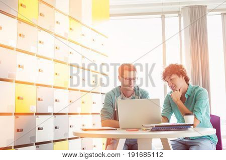 Businessmen using laptop at table in locker room at creative office