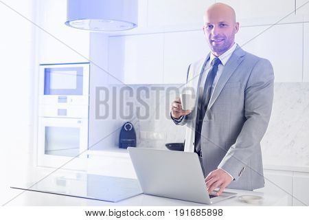 Portrait of confident mid adult businessman having coffee while using laptop in kitchen