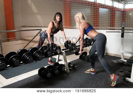 Young Couple Doing Back Exercise With Dumbbells