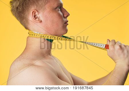 A sporty man with a body meter, a man of sporty appearance on a yellow background.