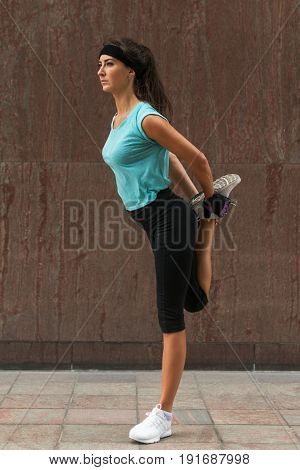 Young fitness woman doing warm-up exercise before running stretching her leg by performing knee to chest stretch on the city street. Sporty athlete preparing legs for cardio workout outdoors.