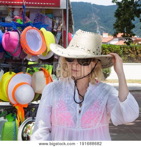 Girl buys sombrero hat in resort town