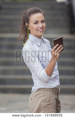 Youth Lifestyle Concepts. Pretty Smiling Caucasian Brunette Woman With Headphones and Chatting on Cellphone. Posing Outdoors