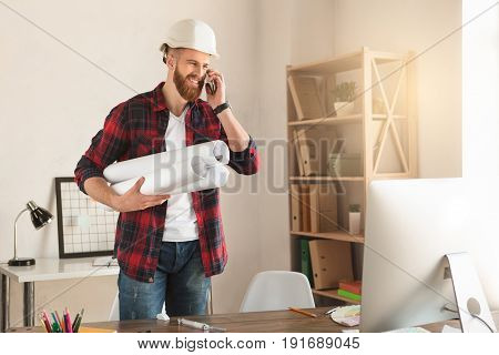 Young male architect working indoors draft blueprint