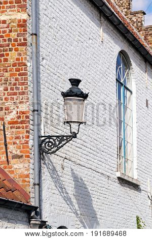 Fragment of the ancient house with a lamp and a window. The brick house of white color a roof from a tile a streetlight at the corner of the house