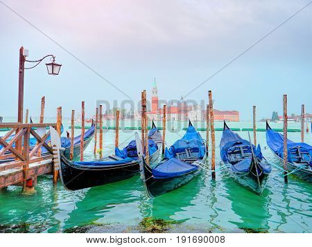 Panoramic view of traditional Gondolas on Canal Grande with San Giorgio Maggiore church in the background