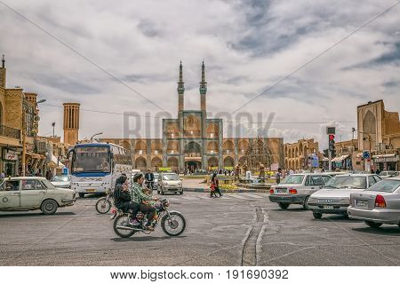 YAZD, IRAN - MAY 5, 2015: Family on a motorcycle passes Amir Chakhmaq Complex mosque and square on cloudy day.