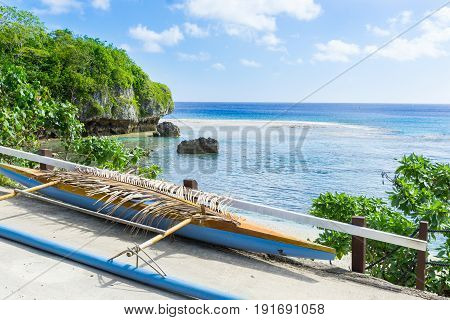 Out-rigger canoe under palm frond to shield some rainwater from boat on ledge overlooking scenic coastline and vast Pacific Island Niue.