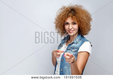 Portrait of beautiful happy curly mixed race girl in casual style is pointing on camera. looking at camera. studio shot on light gray background.