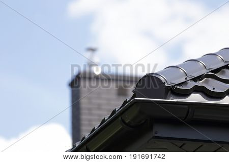 Corner of the new modern house with gutter roof and chimney.