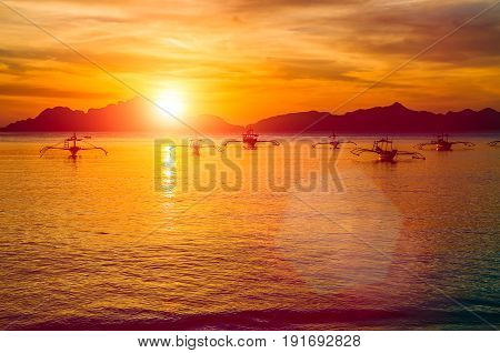 Traditional philippino boats at El Nido bay in sunset lights. Palawan island, Philippines.